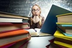 Entsetztes Mädchen, das im offenen Buch schaut Lizenzfreie Stockbilder