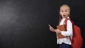 Entsetztes weibliches Kind mit dem Rucksackholdingbuch, Finger auf Tafel zeigend stock footage
