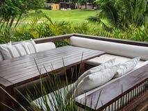 Entspannen Sie sich auf cremefarbenen Kissen und Naturhintergrund Stockbilder