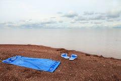 Entspannen Sie sich auf dem Strand - setzen Sie Pantoffel und ein Tuch auf den Strand, um auf einem pebb zu liegen Stockbild