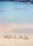 Entspannen Sie sich das Wort, das in den Sand, auf einen schönen Strand mit klaren blauen Wellen im Hintergrund geschrieben wird Stockfoto