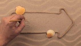ENTSPANNEN Sie sich die Aufschrift, die eigenhändig auf den Sand, in den Zeiger geschrieben wird, der vom Seil gemacht wird stock footage