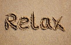 Entspannen Sie sich, geschrieben auf einen Strand. Lizenzfreies Stockbild