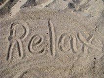 Entspannen Sie sich geschrieben in Sand Lizenzfreies Stockfoto