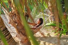 Entspannen Sie sich glückliche Frau auf Sonnenuntergangsonnenaufgang und -kokosnuß des Wiegen- oder Hängemattenstrandhintergrunde Stockfoto