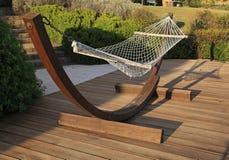 Entspannen Sie sich Hängematte auf hölzerner Terrasse an einem sonnigen Tag Lizenzfreies Stockfoto