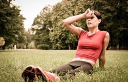 Entspannen Sie sich im Gras - müde Frau nach Sport Stockbild