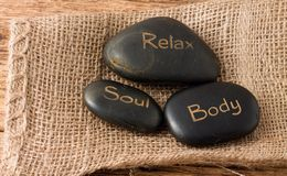 Entspannen Sie sich, Seele, Lavasteine des Körpers drei auf Jutefaserstoff stockfotografie