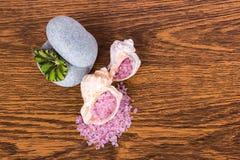 Entspannen Sie sich: Seesalz der rosa Farbe in den Oberteilen und zwei Steine sind auf Th Lizenzfreie Stockbilder