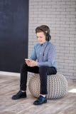 Entspannen Sie sich und hörendes Musikkonzept Europäische Jungenfülle das Stückchen Junge in der Freizeitkleidung stockfotografie