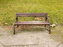 Entspannen Sie sich und nehmen Sie ein Restkonzept Hölzernes Chesterfield mit Metallboden und grünem Gras im Park oder im Garten  Lizenzfreie Stockfotos