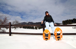 Entspannen Sie sich von der Frau mit Schneeschuhen im Schnee während des Winter holi Stockbilder