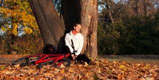 Entspannenc$lehnen des Frauenradfahrers an einem Baum Stockfoto