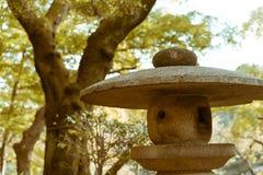 Entspannende alte japanische Steinlaterne gelegen in nationalem Garten Shinjuku Gyoen, Tokyo, Japan Stockbilder