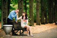 Entspannende Außenseite der schönen schwangeren stilvollen Paare im Herbstpark, der auf Bank sitzt Stockfotografie