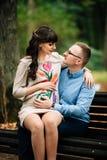 Entspannende Außenseite der schönen schwangeren stilvollen Paare im Herbstpark, der auf Bank sitzt Lizenzfreie Stockfotos