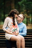 Entspannende Außenseite der schönen schwangeren stilvollen Paare im Herbstpark, der auf Bank sitzt Lizenzfreie Stockbilder