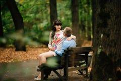 Entspannende Außenseite der schönen schwangeren stilvollen Paare im Herbstpark, der auf Bank sitzt Lizenzfreies Stockfoto