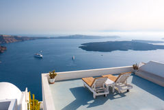 Entspannende Bänke gründeten auf Dachspitze eines Gebäudes in Santorini, Griechenland Stockbilder