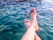 Entspannende Beine eines Mädchens im Meerwasser Lizenzfreie Stockfotos