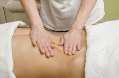 Entspannende Berufsmassage auf dem weiblichen Unterleib im Salon lizenzfreie stockfotos
