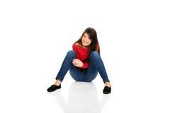 Entspannende Frau, die auf dem Boden sitzt lizenzfreies stockfoto