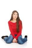 Entspannende Frau, die auf dem Boden sitzt lizenzfreie stockfotos