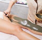 Entspannende Frau, die auf einer Massagetabelle empfängt ein Schlamm treatmen liegt Stockbild