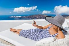 Entspannende Frau, die intelligentes Telefon auf Sofa At Resort verwendet lizenzfreie stockfotos
