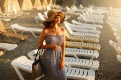 Entspannende Frau mit sunglusses auf dem Genießen der glücklichen Stellung der Sommersonne in einem breiten Sonnenhut am Strand m Stockfotos