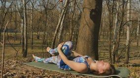 Entspannende Frau, welche draußen die Übungen auf Teppich tut stock footage