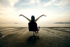 Entspannende Geschäftsfrau, die auf Strand sitzt Stockfotografie