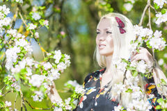 Entspannende kaukasische blonde Frau mit dem langen Haar im Park nahe Blüte Lizenzfreies Stockbild