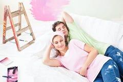 Entspannende Paare, die auf dem Sofa nachdem dem Malen liegen Stockbild