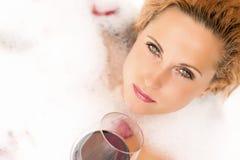 Entspannende sinnliche kaukasische blonde Frau in der schäumenden Badewanne Anhalten eines Glases Rotweins Lizenzfreie Stockbilder