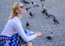 Entspannende Stadtplatz- und Fütterungstauben der Mädchenblondine Frauentouristen- oder -bürgerwurf zerkrümelt für Tauben Mädchen lizenzfreies stockbild