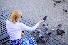 Entspannende Stadtplatz- und Fütterungstauben der Mädchenblondine Frauentouristen- oder -bürgerwurf zerkrümelt für Tauben Mädchen lizenzfreie stockbilder