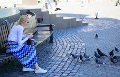 Entspannende Stadtplatz- und Fütterungstauben der Mädchenblondine Frauentouristen- oder -bürgerwurf zerkrümelt für Tauben gruppe lizenzfreies stockfoto