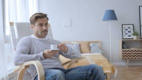 Entspannender erwachsener Mann-trinkender Kaffee beim Sitzen auf zufälligem Stuhl stock video