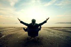 Entspannender Geschäftsmann, der auf Strand sitzt stockfotos