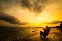 Entspannender Geschäftsmann, der auf Strand sitzt Lizenzfreies Stockfoto