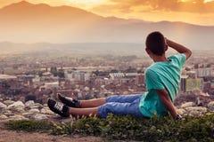 Entspannender Junge, der zur Stadt schaut Lizenzfreie Stockfotos