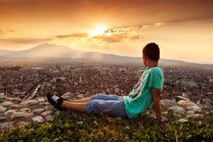 Entspannender Junge, der zur Stadt schaut Stockfoto