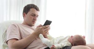 Entspannender Mann, der Telefon mit Baby auf Knien verwendet stock video footage