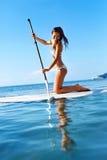 Entspannender Wasser-Sport Frau, die auf Brandungs-Brett schaufelt Sommer Lizenzfreie Stockfotos
