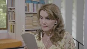 Entspannendes Buch der reizend Studentenfrau Lese, beim Hören Musik in einer Bibliothek - stock video