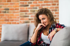 Entspannendes Frauensitzen bequem im lächelnden glücklichen schauenden Kamerastillstehen des Sofaklubsessels lizenzfreies stockbild