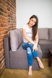 Entspannendes Frauensitzen bequem im lächelnden glücklichen schauenden Kamerastillstehen des Sofaklubsessels lizenzfreie stockfotos