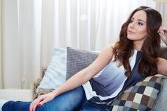 Entspannendes Frauensitzen bequem im Sofaaufenthaltsraum lizenzfreies stockbild