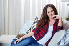 Entspannendes Frauensitzen bequem im Sofaaufenthaltsraum lizenzfreie stockbilder